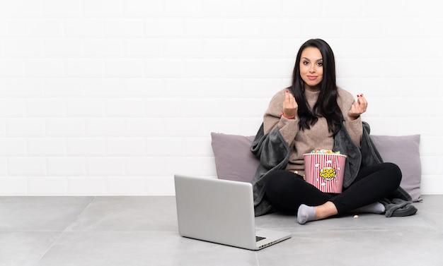 Giovane ragazza colombiana che tiene una ciotola di popcorn e che mostra un film in un computer portatile che fa gesto di soldi