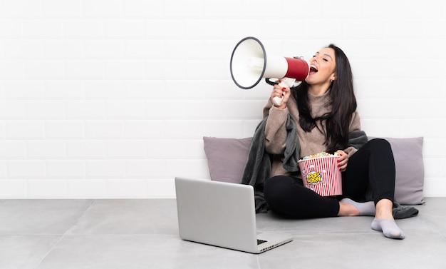 Giovane ragazza colombiana che tiene una ciotola di popcorn e che mostra un film in un computer portatile che grida tramite un megafono