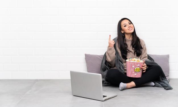 Giovane ragazza colombiana che tiene una ciotola di popcorn e che mostra un film in un computer portatile che indica una grande idea