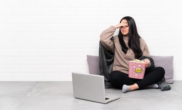 Giovane ragazza colombiana che tiene una ciotola di popcorn e che mostra un film in un computer portatile con espressione stanca e malata