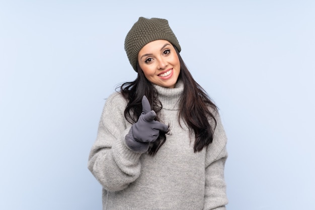 Giovane ragazza colombiana con cappello invernale punta il dito su di te