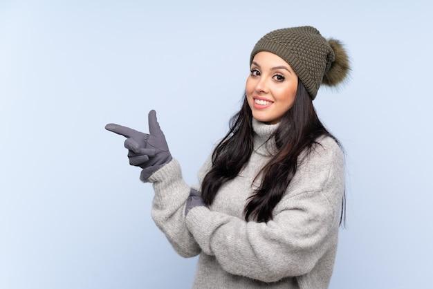Giovane ragazza colombiana con cappello invernale sul muro blu che punta il dito verso il lato