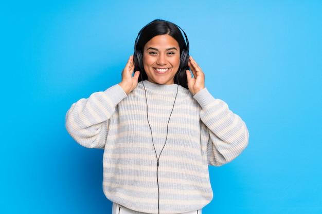 Giovane ragazza colombiana con maglione che ascolta la musica con le cuffie