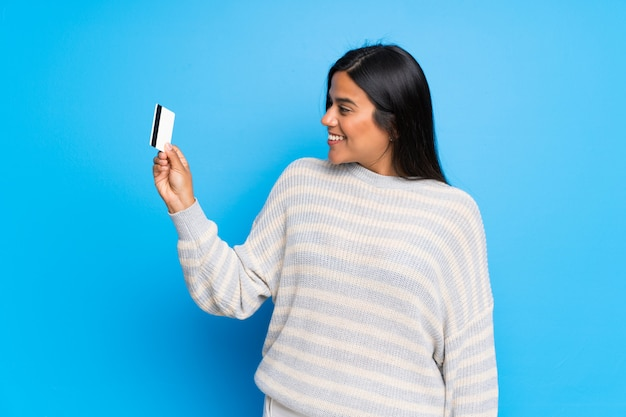 Giovane ragazza colombiana con maglione in possesso di una carta di credito e di pensare