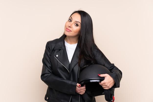 Giovane ragazza colombiana in possesso di un casco da motociclista sul muro ridendo