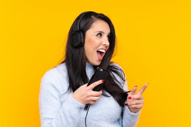 Giovane ragazza colombiana sul muro giallo ascoltando musica con un cellulare e cantando