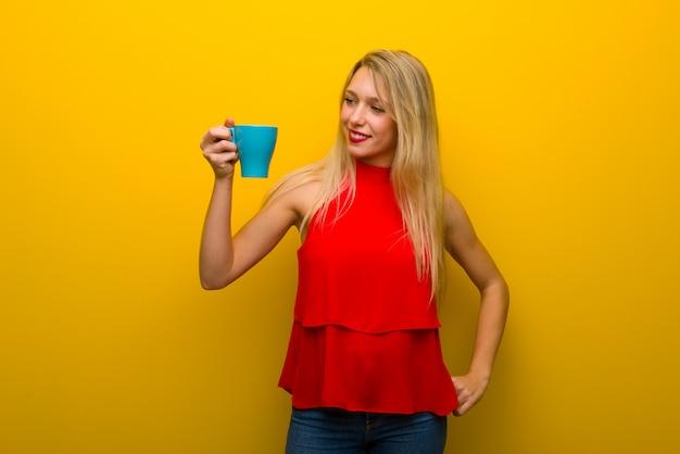 Giovane ragazza con abito rosso sulla parete gialla in possesso di una tazza di caffè caldo
