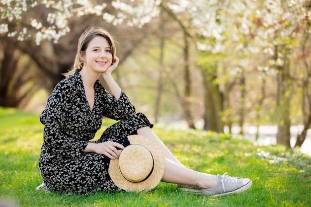 Giovane ragazza con cappello seduto vicino a un albero in fiore nel parco.