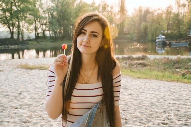 Giovane ragazza con i capelli lunghi sulla spiaggia durante il tramonto. abbagliamento solare