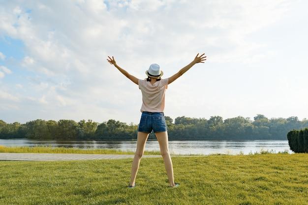 Giovane ragazza con la schiena nel cappello sulla riva del fiume, allargò le mani ai lati