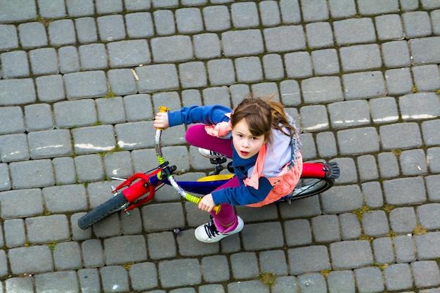 Giovane ragazza con lunghi capelli castano chiaro in sella a una bicicletta