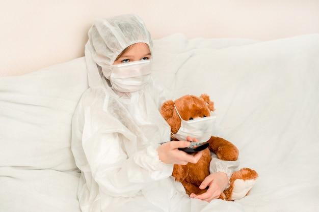 Giovane ragazza con orsacchiotto, in maschera e un abito medico bianco, sdraiarsi sul letto e guardare la tv, concept quarantine, rimanere a casa