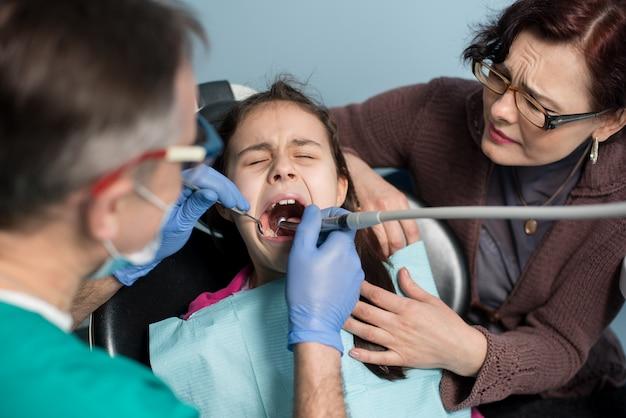 Giovane ragazza con sua madre alla prima visita dentale. dentista pediatrico senior che tratta i denti pazienti della ragazza