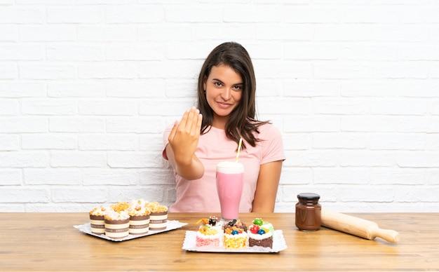 Giovane ragazza con tante mini torte diverse che invitano a venire
