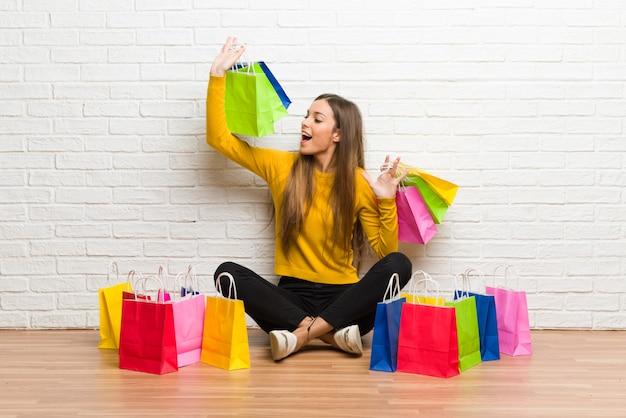 Giovane ragazza con un sacco di borse per la spesa