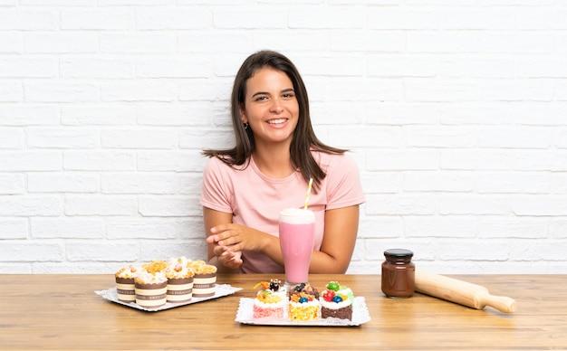 Giovane ragazza con un sacco di diverse mini torte applaudire
