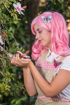 Giovane ragazza con una parrucca rosa in posa come nel parco