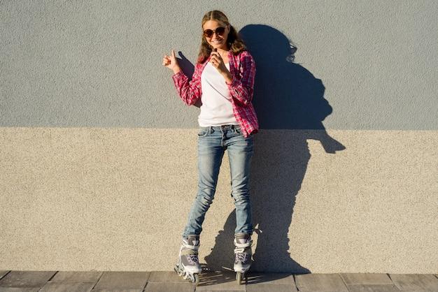 Giovane ragazza cool, calzata nei rollerblade che tengono la barra di cioccolato