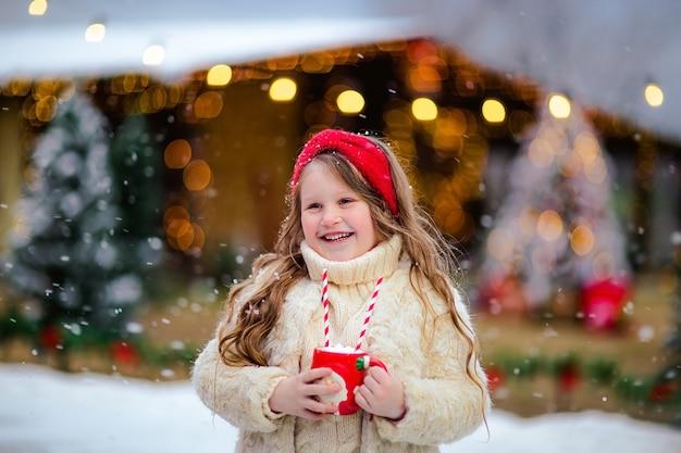 Giovane ragazza dai capelli abbastanza lunghi che propone con la tazza di natale alla pista di pattinaggio aperta. sfondo di natale.