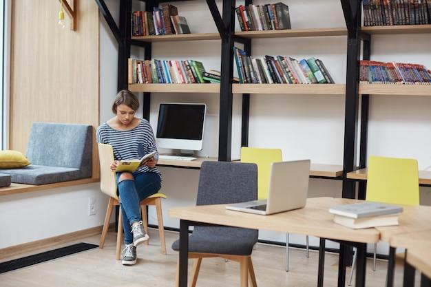 Giovane ragazza dai capelli chiari intelligente con acconciatura bob in abiti casual, seduta sulla sedia in biblioteca moderna, leggendo il libro preferito, rilassarsi dopo una lunga giornata di studio