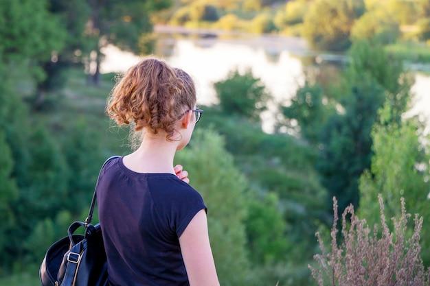 Giovane ragazza dalla collina guardando il fiume. la ragazza è nella natura. ammirando la bellezza della natura