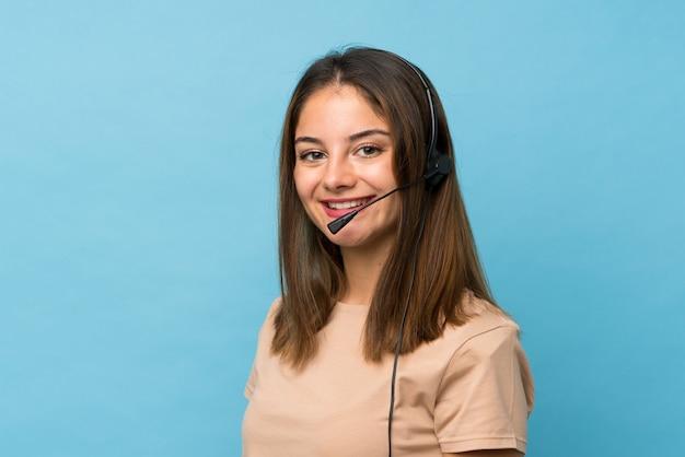 Giovane ragazza del brunette sopra lavorare blu isolato con la cuffia avricolare