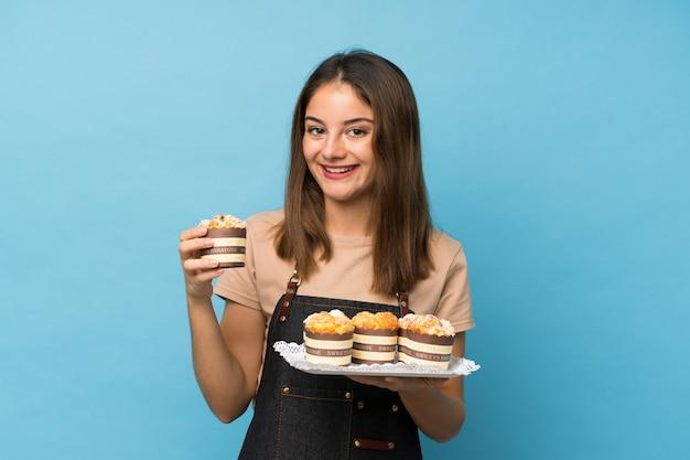 Giovane ragazza del brunette sopra le mini torte della holding blu isolata