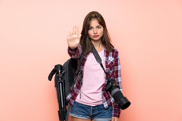 Giovane ragazza del fotografo che fa gesto di arresto con la sua mano