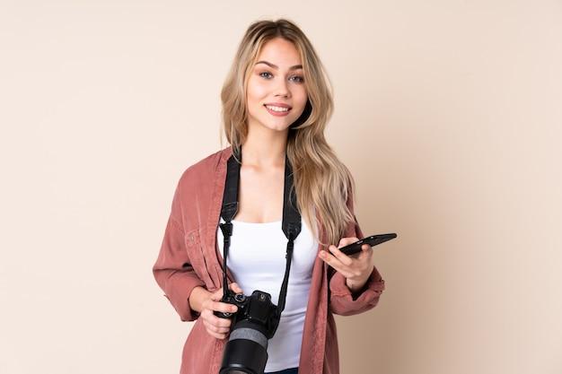 Giovane ragazza del fotografo sopra caffè isolato della tenuta da portare via e un cellulare