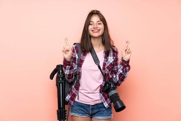 Giovane ragazza del fotografo sopra la parete rosa isolata con l'incrocio delle dita