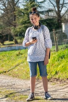Giovane ragazza dell'adolescente che aspetta lo scuolabus