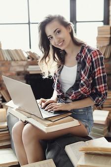 Giovane ragazza dell'adolescente che per mezzo del computer portatile circondato da molti libri.