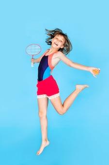 Giovane ragazza dell'adolescente che salta e che gioca volano sulla parete blu