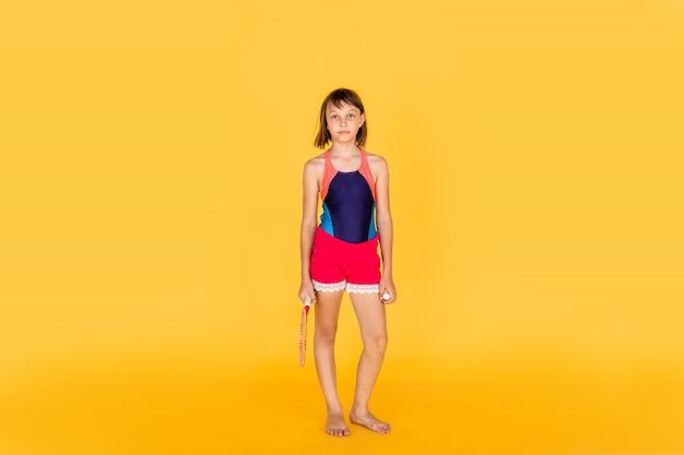 Giovane ragazza dell'adolescente che salta e che gioca volano sulla parete gialla