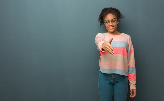 Giovane ragazza dell'afroamericano con gli occhi azzurri che raggiungono fuori per accogliere qualcuno