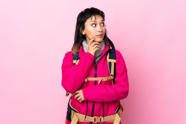 Giovane ragazza dell'alpinista con un grande zaino sopra il rosa isolato che pensa un'idea