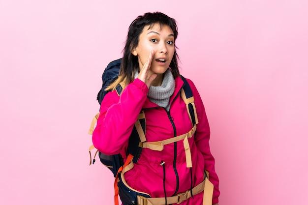Giovane ragazza dell'alpinista con un grande zaino sopra il sussurro rosa isolato qualcosa