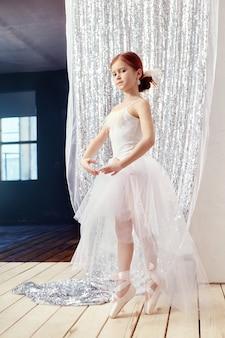 Giovane ragazza della ballerina che prepara prestazione di balletto