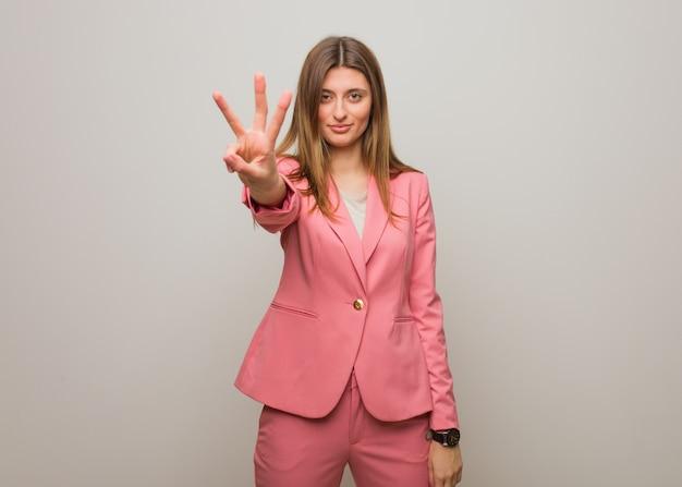 Giovane ragazza della donna di affari che mostra numero tre