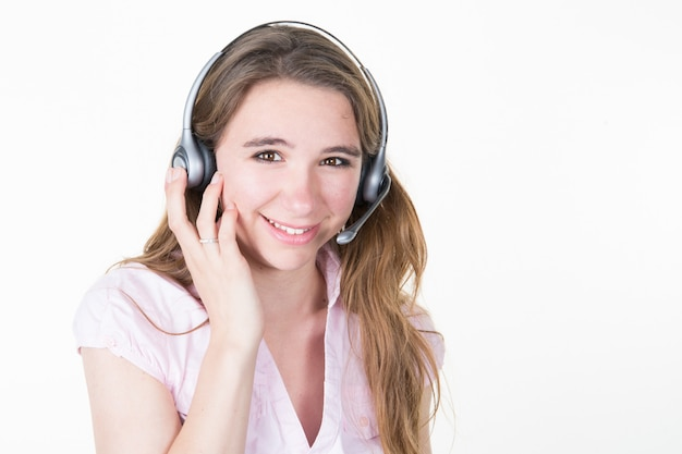 Giovane ragazza della studentessa di affari con la cuffia avricolare in operatore felice e sorridente dell'ufficio servizio clienti isolato su fondo bianco