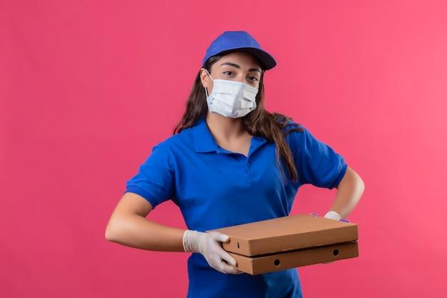 Giovane ragazza delle consegne in uniforme blu e cappuccio che indossa la maschera protettiva per il viso e guanti tenendo le scatole per pizza guardando la fotocamera con espressione facciale seria fiduciosa in piedi sopra backgroun rosa