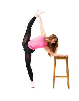 Giovane ragazza di ballo sopra l'allungamento bianco isolato della priorità bassa