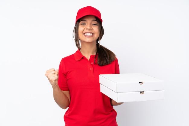 Giovane ragazza di consegna della pizza sopra bianco che celebra una vittoria nella posizione del vincitore