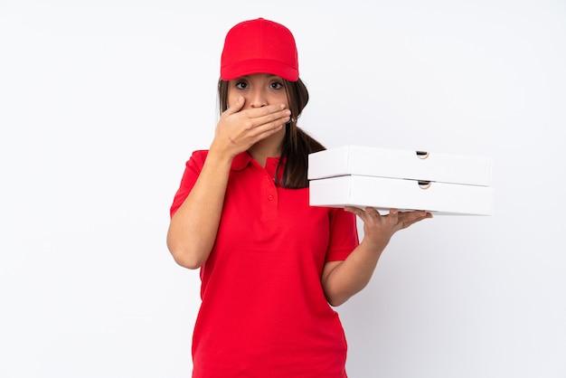Giovane ragazza di consegna della pizza sopra la bocca bianca isolata del rivestimento murale con le mani