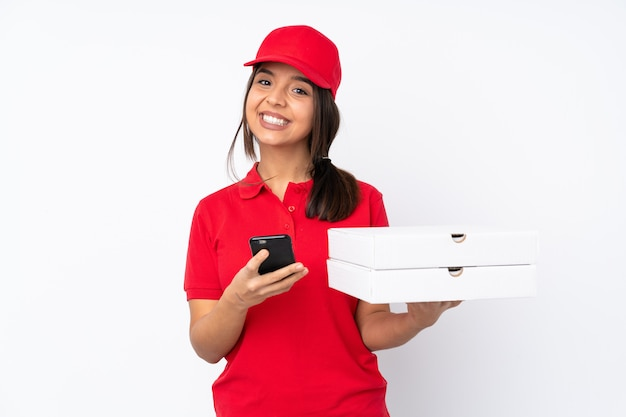 Giovane ragazza di consegna della pizza sopra la parete bianca isolata che invia un messaggio con il cellulare