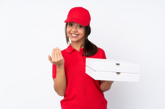 Giovane ragazza di consegna della pizza sopra la parete bianca isolata che invita a venire con la mano. felice che tu sia venuto