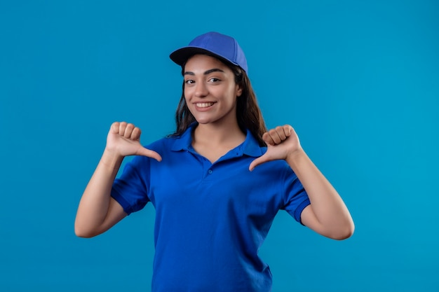 Giovane ragazza di consegna in uniforme blu e berretto cercando fiducioso che punta a se stessa con il pollice soddisfatto di sé e orgoglioso in piedi su sfondo blu