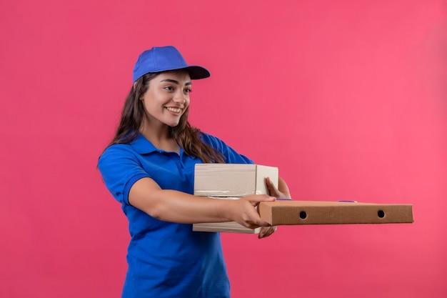 Giovane ragazza di consegna in uniforme blu e cappuccio che dà le scatole di cartone ad un cliente che sorride amichevole che sta sopra fondo rosa
