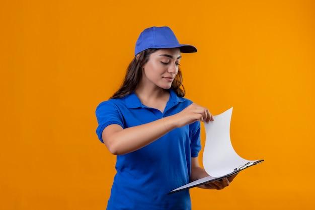 Giovane ragazza di consegna in uniforme blu e cappuccio che tiene appunti guardandolo con seria espressione sicura sul viso in piedi su sfondo giallo