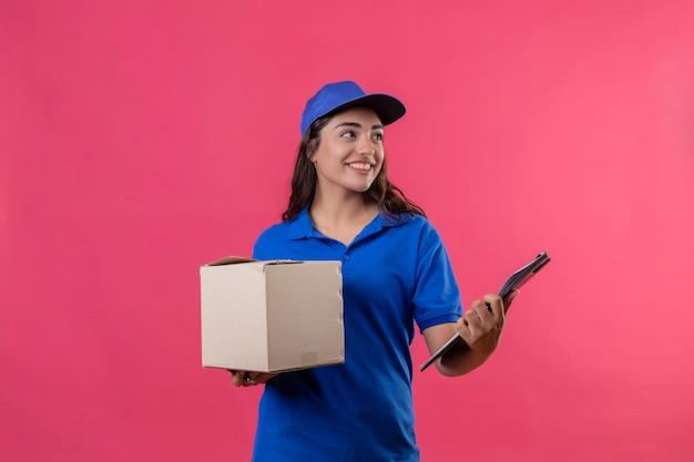 Giovane ragazza di consegna in uniforme blu e cappuccio che tiene il pacchetto della scatola e negli appunti che osserva da parte sorridendo allegramente in piedi su sfondo rosa